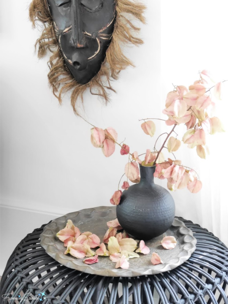 Vignette of Woven Side Table, Carved Mask, Vase and Dried Flowers.   @FanningSparks